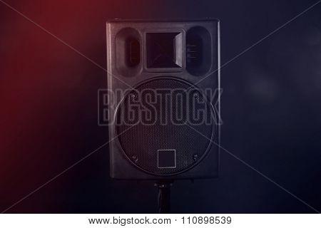 Black loudspeaker on dark colourful background