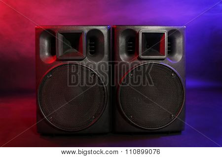 Big black loudspeakers on colourful background, close up