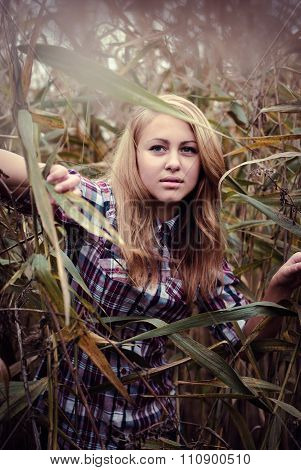 Beautiful young woman in plated shirt standing among sedge leaves