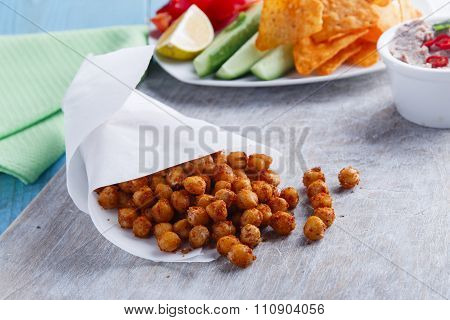 Roasted spicy chickpeas on rustic background scattered