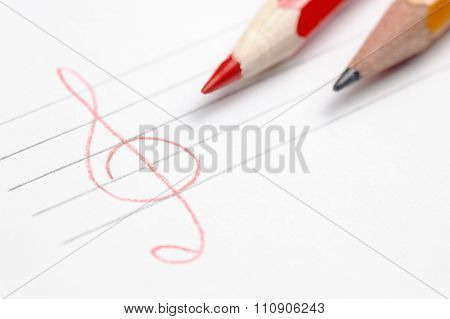 White paper sheet with two pencils and hand drawn stave and treble clef shallow depth of field have