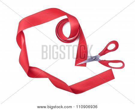 Scissors cuts red ribbon.