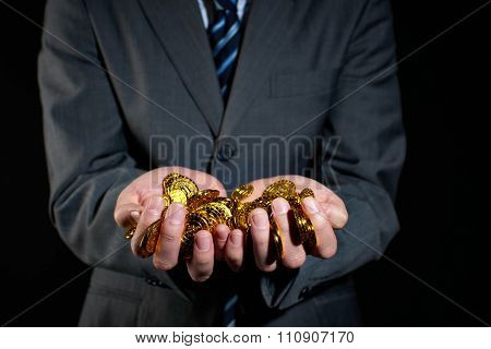 Businessman holding gold coins isolated on black