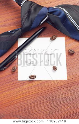 Paper sheet with handwritten words Coffee Break decorated with scattered coffee beans, neck tie and
