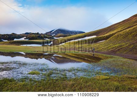 Early summer morning in the National Park Landmannalaugar, Iceland. Snow lies in the hollows of colorful rhyolite mountains. Green Valley is flooded with melt water