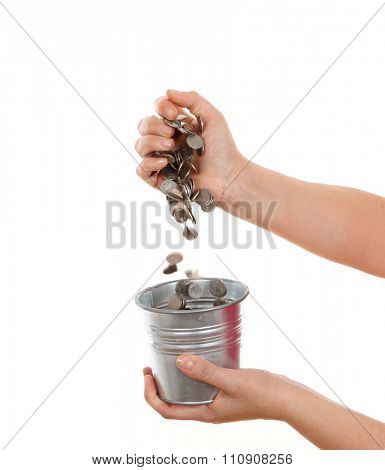 pouring coins into the bucket isolated on white background