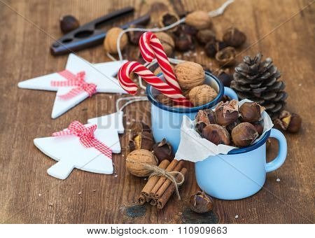 Traditional Christmas foods and decoration. Roasted chestnuts in blue  enamel mug, walnuts, cinnamon