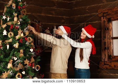 Cheerful Couple Decorates A Christmas Tree In A Country House