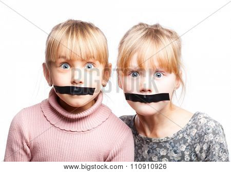 Portrait of two little girls with duct tape on their mouths - silenced child concept