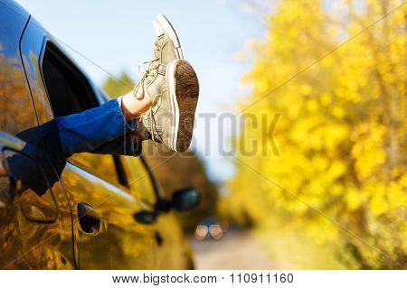 boy's legs in sneakers in the window car