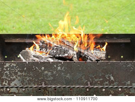 Burning embers in brazier against green grass background