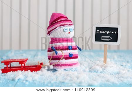 Signpost of the famous ski resort Zakopane, Poland and Snowman with red sled stand near direction si
