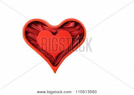 Red painted wooden heart enclosed with red paper raffia strips in red box isolated on white backgrou