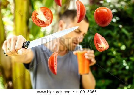 Man Drinks Tomato Juice And Cuts Tomatoes Simultaneously.