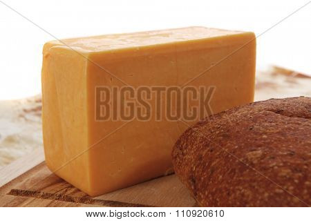 aged italian cheddar cheese on wooden board with rye ciabatta on used baking paper as background