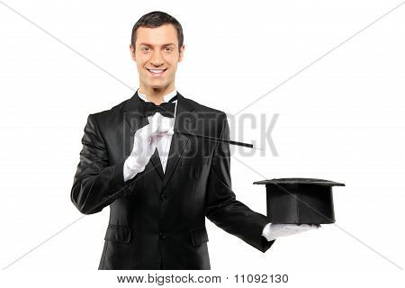 A Magician In A Black Suit Holding An Empty Top Hat And Magic Wand