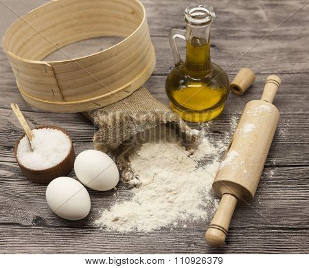 Wheat flour in a canvas bag,sieve, the olive oil in a glass carafe, a large salt shaker wood, raw eggs, a wooden rolling pin: set for making homemade bread dough on a beautiful dark wooden background.