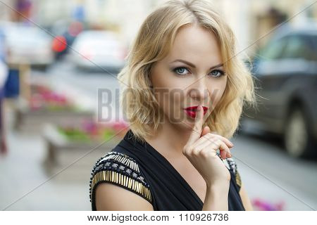 Young beautiful blonde woman has put forefinger to lips as sign of silence, outdoors
