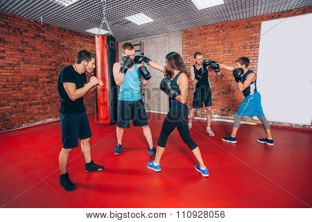 Boxing aerobox group with personal trainer man at fitness gym, gloves, punching bag