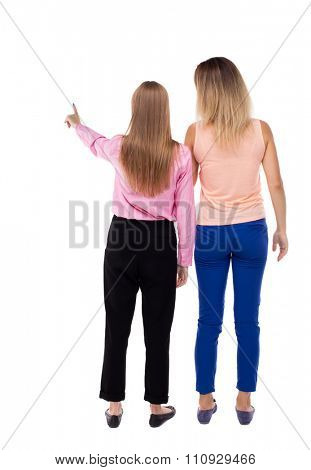 Back view of two pointing young girl. Rear view people collection.  backside view of person.  Rear view. Isolated over white background. Two girls stand together looking at something.