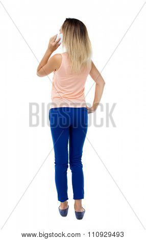 back view of a woman talking on the phone.  backside view of person.  Rear view people collection. Isolated over white background. Blonde in blue trousers pressed to his ear listening to the phone.