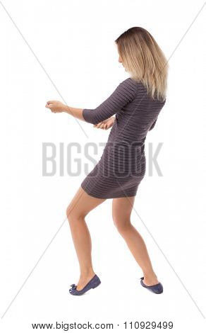 back view of standing girl pulling a rope from the top or cling to something. girl  watching.  backside view of person.  Isolated over white background. Blonde in a short dress pulls the rope on left.