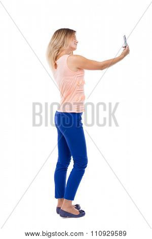 back view of standing young beautiful  woman  and using a mobile phone. girl  watching. backside view of person.  Isolated over white background. Blonde in blue pants makes self smartphone on white.