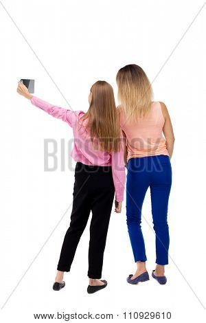Back view of two young woman photographed on a mobile phone. Rear view people collection.  backside view of person. Rear view. Isolated over white background. Two girls blonde doing self Tablet PC.