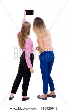 Back view of two young woman photographed on a mobile phone. Rear view people collection. Rear view. Isolated over white background. Two girls blonde make self raising high over a Tablet PC.