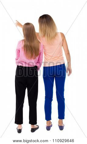 Back view of two pointing young girl. Rear view people collection.  backside view of person. Rear view. Isolated over white background. One girl shows another something away.