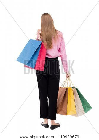 back view of woman with shopping bags . beautiful brunette girl in motion.  backside view of person.   girl in the pink shirt is thrown over his left shoulder bags with purchases.