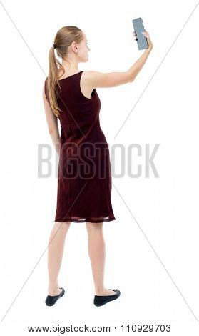 back view of standing young beautiful  girl with tablet computer in the hands of. girl  watching.  Isolated over white background. The blonde burgundy dress keeps self on your tablet.