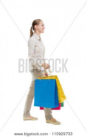 back view of going  woman  with shopping bags . beautiful girl in motion.  backside view of person. Isolated over white background. Girl in gray jeans goes away smiling and carries a handbag.