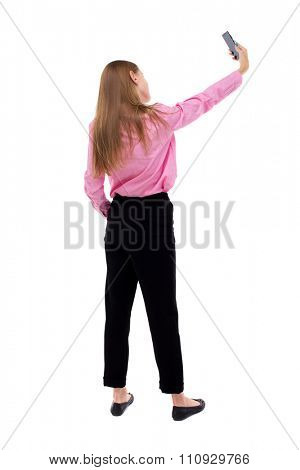 back view of standing young beautiful  woman  and using a mobile phone. girl  watching.  backside view of person.  Isolated over white background.  Turning right takes the girl self.