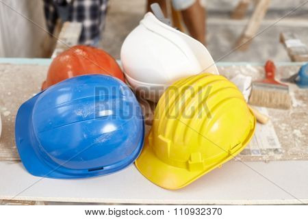 Closeup photo of hardhats of different colours.