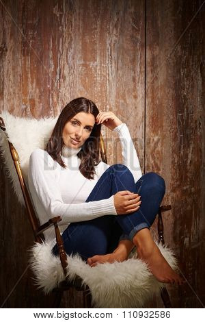 Attractive casual woman sitting in chair with pulled up legs, front of antique wooden wall.
