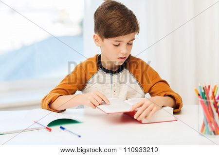 education, childhood, people, homework and school concept - student boy reading book or textbook at home