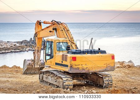 Excavator loader machine with sunset background.