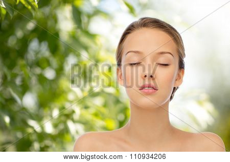 beauty, people, organic, eco and health concept - young woman face with closed eyes and shoulders over green natural background