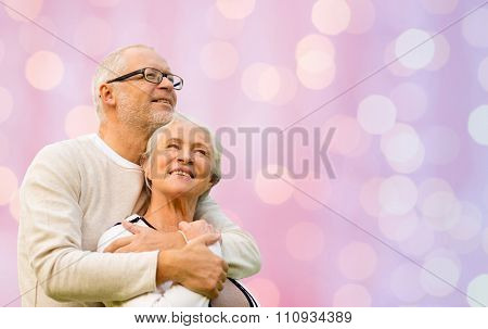 family, love, age and old people concept - happy senior couple hugging over pink holidays lights background