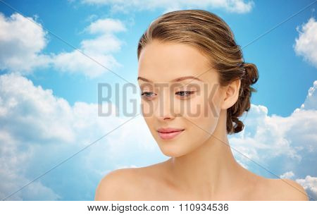 beauty, people and health concept - smiling young woman face and shoulders over blue sky and clouds background