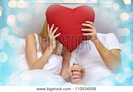 people, love, valentines day, holidays and happiness concept - happy couple in bed hiding faces behind red heart shape pillow over lights background