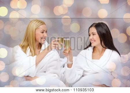 travel, celebration, friendship and holidays concept - smiling girlfriends in bathrobes with champagne glasses in bed at hotel over lights background