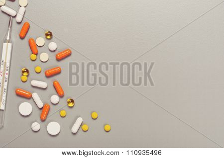 Scattered Pills On A Gray Table With Thermometer