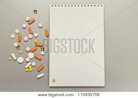 Open Notebook On Gray Table With Pills And Capsules