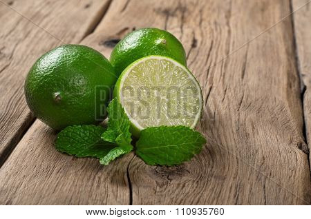 Fresh Limes With Mint Leaves On Wooden Table