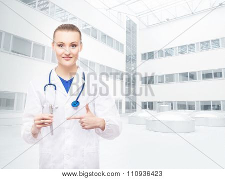 Young, professional and cheerful female doctor suggests using electronic cigarettes over hospital background.