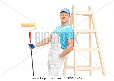 Young male decorator holding a paint roller and leaning on a wooden ladder isolated on white background