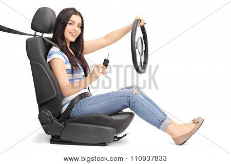 Young woman holding a car key and a steering wheel seated on a car seat isolated on white background