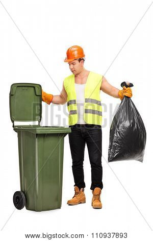 Full length portrait of a male waste collector picking up a bag from a trash can isolated on white background
